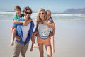Portrait of smiling parents piggybacking their children at beach Royalty Free Stock Photo
