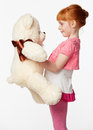 Portrait of a smiling redheaded girl in a pink shirt hugging the Royalty Free Stock Photo