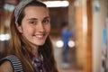 Portrait of smiling schoolgirl standing near notice board in corridor Royalty Free Stock Photo