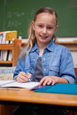 Portrait of a smiling schoolgirl writing Stock Image