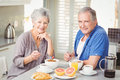 Portrait of smiling senior couple having breakfast at table Royalty Free Stock Photo