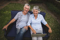 Portrait of smiling senior couple sitting with laptop on couch in backyard Royalty Free Stock Photo