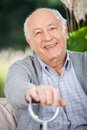 Portrait of smiling senior man holding walking stick while sitting on couch in nursing home porch Royalty Free Stock Images