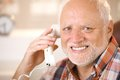 Portrait of smiling senior using landline phone closeup man looking at camera Stock Images