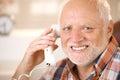 Portrait of smiling senior using landline phone Royalty Free Stock Photo