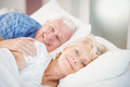 Portrait of smiling senior woman relaxing besides man on bed women men in room Stock Photo