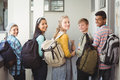 Portrait of smiling students standing with notebook and school bag in corridor Royalty Free Stock Photo
