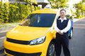 Portrait of smiling taxi driver with car