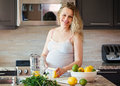 Portrait of smiling white Caucasian blonde pregnant woman cutting citrus lime lemon making juice standing in kitchen Royalty Free Stock Photo