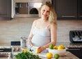 Portrait of smiling white Caucasian blonde pregnant woman cutting citrus lime lemon making juice standing in kitchen