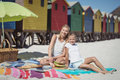 Portrait of smiling woman with her daughter sitting on blanket at beach Royalty Free Stock Photo