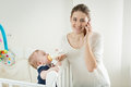 Portrait of smiling woman talking by phone while feeding her bab Royalty Free Stock Photo