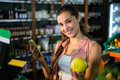 Portrait of smiling woman using her phone while buying fruits in organic section Royalty Free Stock Photo