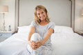 Portrait of smiling women sitting with legs crossed on bed Royalty Free Stock Photo