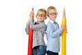 Portrait smiling young boys in glasses and bowtie posing near huge colorful pencils. Educational concept. Isolated over white. Royalty Free Stock Photo