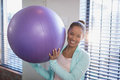 Portrait of smiling young female doctor holding purple exercise ball Royalty Free Stock Photo