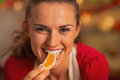 Portrait of smiling young housewife eating orange Royalty Free Stock Photo