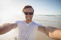 Portrait of smiling young man wearing sunglasses at beach Royalty Free Stock Photo