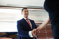 Portrait of a smiling young managing director shaking hands with his business partners while standing in office space interior Royalty Free Stock Photo