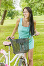 Portrait of smiling young woman with bicycle in the park Royalty Free Stock Images