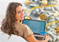 Portrait of smiling young woman with credit card and laptop in fr Royalty Free Stock Photo