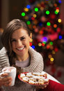 Portrait of smiling young woman with cup of hot beverage and christmas cookies near christmas tree Royalty Free Stock Photos