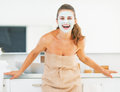 Portrait of smiling young woman with facial mask in bathroom modern Royalty Free Stock Photo