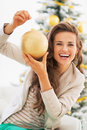 Portrait of smiling young woman holding christmas ball in living room Royalty Free Stock Photography