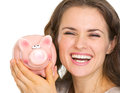Portrait of smiling young woman holding piggy bank Stock Photos