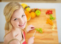 Portrait of smiling young woman making fruits salad in modern kitchen Royalty Free Stock Images
