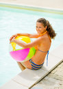 Portrait of smiling young woman near swimming pool with ball sitting Stock Photography