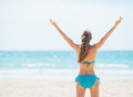 Portrait of smiling young woman rejoicing on beach rear view in swimsuit Royalty Free Stock Photography