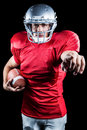 Portrait of sportsman pointing while holding american football against black background Stock Image