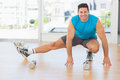 Portrait of a sporty man doing stretching exercise full length in fitness studio Royalty Free Stock Photo