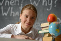 Portrait of a student smilind happy or schoolgirl siting at desk against blackboard Royalty Free Stock Photos