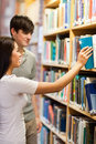 Portrait of students choosing a book on a shelf Royalty Free Stock Images