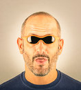 Portrait of a stupid man with too small sunglasses which appear to be to Royalty Free Stock Photography