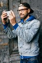 Portrait of stylish guy with beard wearing trendy clothes holding mobile phone making selfie being pleased and smiling with joy in Royalty Free Stock Photo