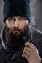 Portrait of a stylish man with beard and pipe the smoking looks like sailor captain wearing thick sweater black cap Stock Images