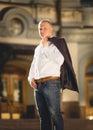 Portrait of stylish man on street holding jacket over shoulder Royalty Free Stock Photo