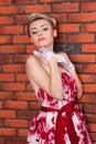 Portrait of stylish woman in a vintage dress near brick wall