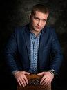 Portrait of a successful business man with his hands folded on dark background Royalty Free Stock Photos