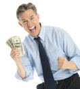 Portrait of successful businessman showing one hundred dollar bi mature bills while standing against white background Royalty Free Stock Photography
