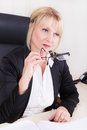 Portrait of a successful older businesswoman with glasses succesful sitting in her office in her hand Stock Image