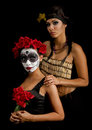 Portrait of a sugar skull and american indian two beautiful young women one with makeup red flowers in her hair the second Royalty Free Stock Image