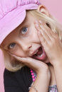 Portrait of a surprise young girl with hands on face over pink background Stock Images