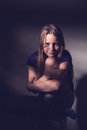 Portrait of a teen girl sitting on a chair in a dark room, contr Royalty Free Stock Photo