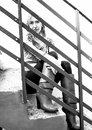 Portrait of teen girl sitting on stairs behind metal railings Stock Images