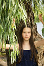 Portrait of teen girl standing under the branches of aspen and m