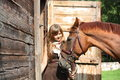 Portrait of teenage girl and chestnut horse near the wooden stab stable in summer Stock Photo